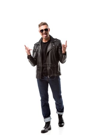 excited stylish man in leather jacket showing rock signs and sticking out tongue isolated on white