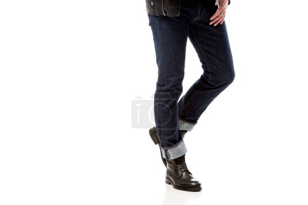 partial view of stylish man wearing denim and leather boots isolated on white