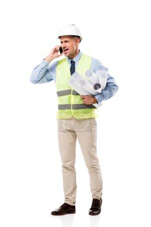 Foto de Satisfecho Ingeniero sosteniendo blueprints y hablando por teléfono inteligente aislado en blanco - Imagen libre de derechos