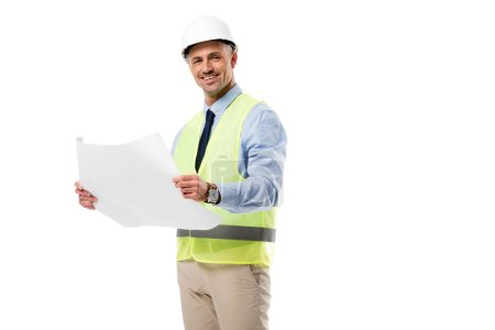 handsome engineer in helmet looking at camera and holding blueprint isolated on white
