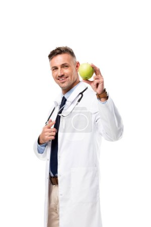 Photo for Smiling doctor pointing with finger at green apple isolated on white, healthy eating concept - Royalty Free Image