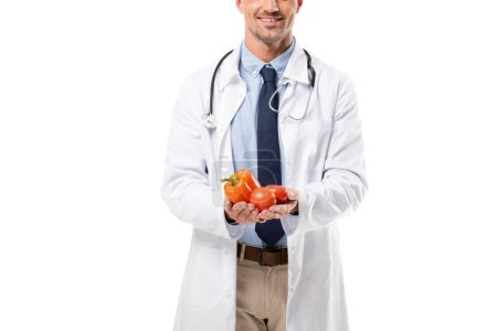 partial view of doctor holding vegetables in hands isolated on white, healthy eating concept