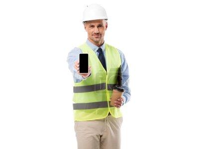 Foto de Apuesto Ingeniero sosteniendo el smartphone con la pantalla en blanco y café para ir aislado en blanco - Imagen libre de derechos