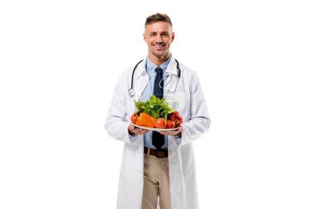 Photo pour Médecin regardant la caméra et tenant la plaque de légumes frais isolés sur blanc, concept de saine alimentation - image libre de droit