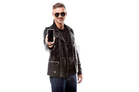 Photo pour Homme adulte chic en veste de cuir présentant des smartphone avec écran blanc isolé sur blanc - image libre de droit