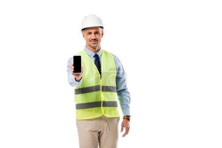 Foto de Ingeniero sonriente mirando a cámara y sujetando el smartphone con la pantalla en blanco aislada en blanco - Imagen libre de derechos
