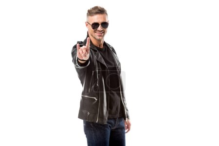 Photo for Smiling man in leather jacket and sunglasses showing rock sign isolated on white - Royalty Free Image