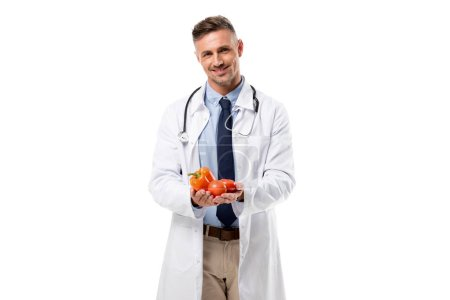 Photo pour Docteur sourire regardant la caméra et la tenue des légumes en mains isolés sur blanc concept manger sain - image libre de droit