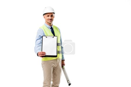 handsome engineer holding clipboard with blank sheet and spirit level isolated on white