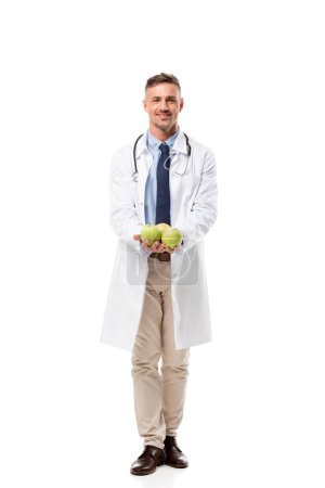Photo for Smiling doctor looking at camera and holding fresh apples isolated on white, healthy eating concept - Royalty Free Image