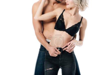 Teilansicht des hemdlosen Mannes, der die Jeans der Frau aufreißt, isoliert auf Weiß