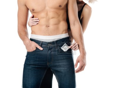 cropped view of woman hugging shirtless man from behind and holding condom isolated on white, safe sex concept