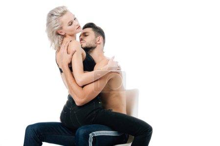 Photo pour Beau couple passionné assis sur la chaise et embrassant isolé sur blanc - image libre de droit