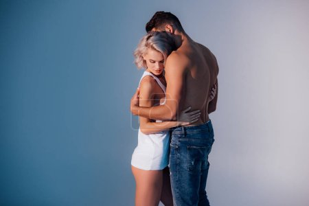 young heterosexual couple embracing on dark blue background