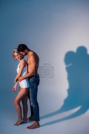 shirtless man hugging woman from behind with shadows on dark blue background