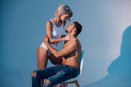 beautiful young woman passionately looking at man sitting on chair with dark blue background