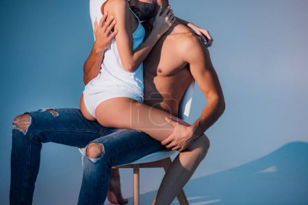 cropped view of heterosexual couple sitting on chair and hugging on dark blue background