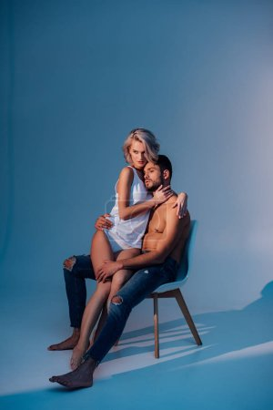 attractive woman and man sitting on chair, hugging and looking away on dark blue background