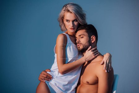 attractive woman and man hugging and looking away on dark blue background