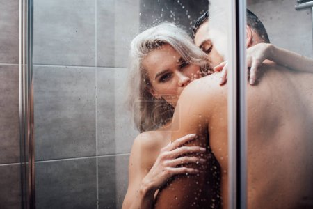 Photo pour Homme passionné embrassant et embrassant belle femme dans la douche - image libre de droit