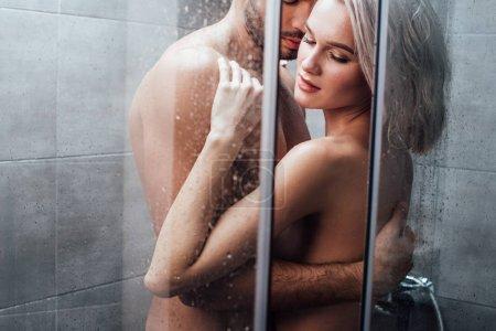 Photo pour Homme embrassant passionnément femme attrayante dans la douche - image libre de droit
