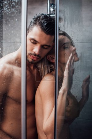Photo for Beautiful naked couple embracing in passion and taking shower together - Royalty Free Image