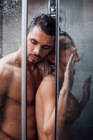 Foto de Hermosa pareja desnuda abrazando en pasión y tomando ducha juntos - Imagen libre de derechos