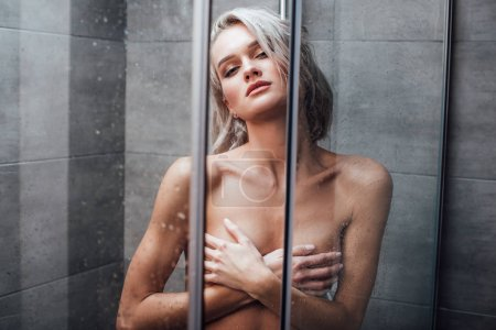 beautiful naked woman covering breasts and posing while taking shower in bathroom