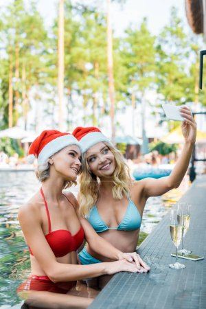 Photo for Smiling friends in santa claus hats taking selfie on smartphone in swimming pool, new year concept - Royalty Free Image