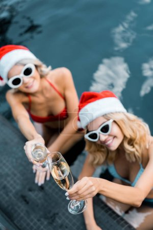overhead view of happy women in santa claus hats clinking glasses of champagne while relaxing in swimming pool, new year celebration concept