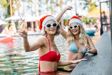 happy women in santa claus hats and sunglasses with glasses of champagne resting in swimming pool, new year celebration concept