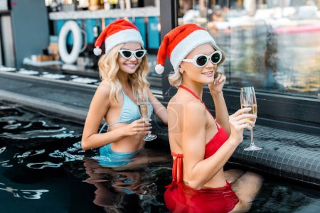 beautiful women in santa claus hats and sunglasses with glasses of champagne resting in swimming pool, new year celebration concept