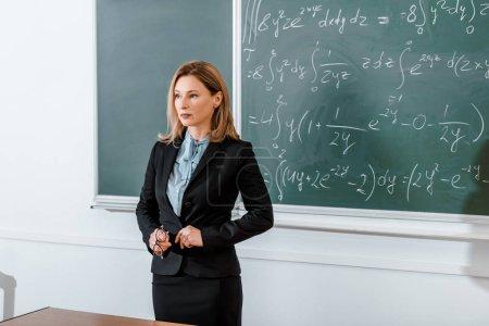 Female teacher standing in formalwear near chalkboard and holding glasses