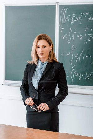 Beautiful teacher standing in classroom and holding glasses