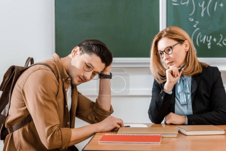 Photo pour Jeune étudiante assise avec sac à dos près d'une enseignante et tenant la tête - image libre de droit