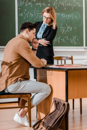 Photo for Female professor standing with crossed arms and looking at thoughtful student in classroom - Royalty Free Image