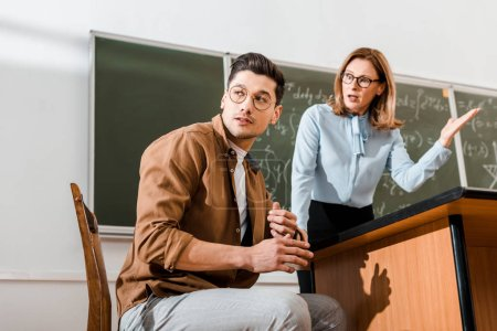 Dissatisfied female teacher standing near chalkboard and speaking with student in classroom