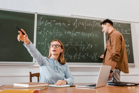 Female teacher sitting at desk and pointing at something in classroom