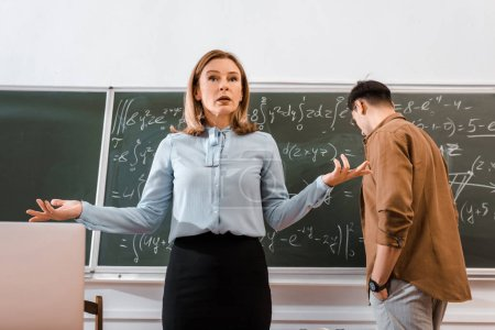 Female teacher gesturing in classroom in formalwear near student