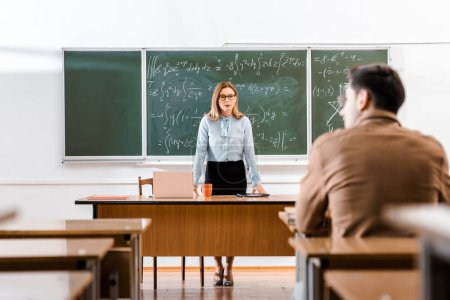 Female lecturer standing at desk near chalkboard with equations in class