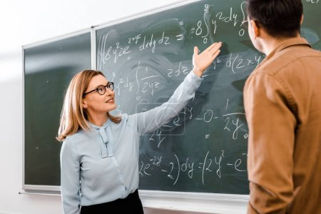 Female professor showing equations in classroom