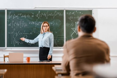 Teacher pointing at equations in classroom with student