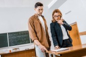 focused female teacher helping male student with assignment during lesson in classroom