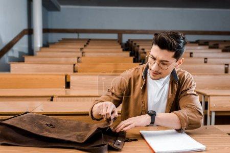 Photo pour Élève de sexe masculin ciblée dans des verres, assis au bureau et à la recherche de stylo dans le sac en cuir au cours de la leçon en classe - image libre de droit