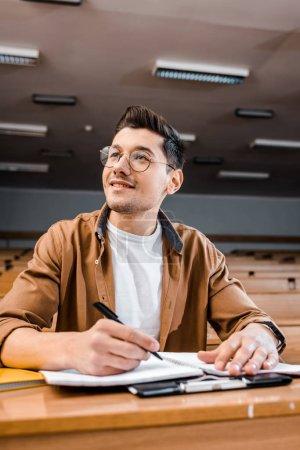 Photo pour Étudiant souriant dans des lunettes assis au bureau et écrivant dans un cahier pendant les cours en classe - image libre de droit