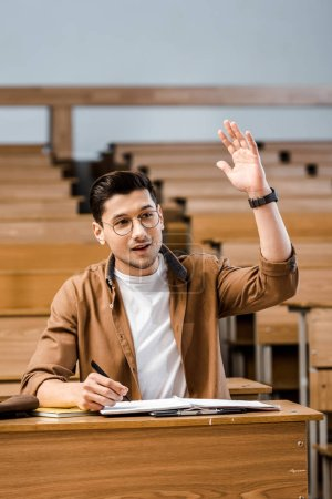 handsome smiling male student in glasses sitting at desk and raising hand during lesson in classroom
