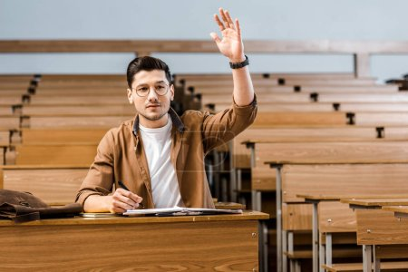 focused male student in glasses sitting at desk and raising hand during lesson in classroom