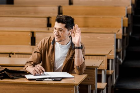 smiling male student in glasses sitting at desk and raising hand during lesson in classroom