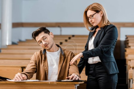 female university teacher looking at male student in glasses writing exam in classroom