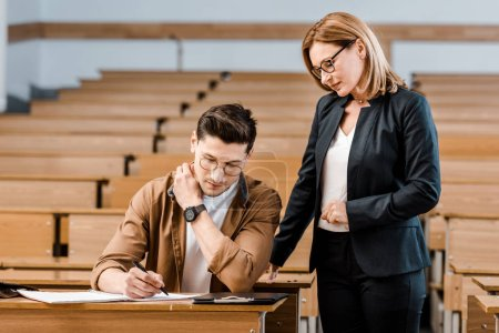 female university teacher looking at male student writing exam in classroom